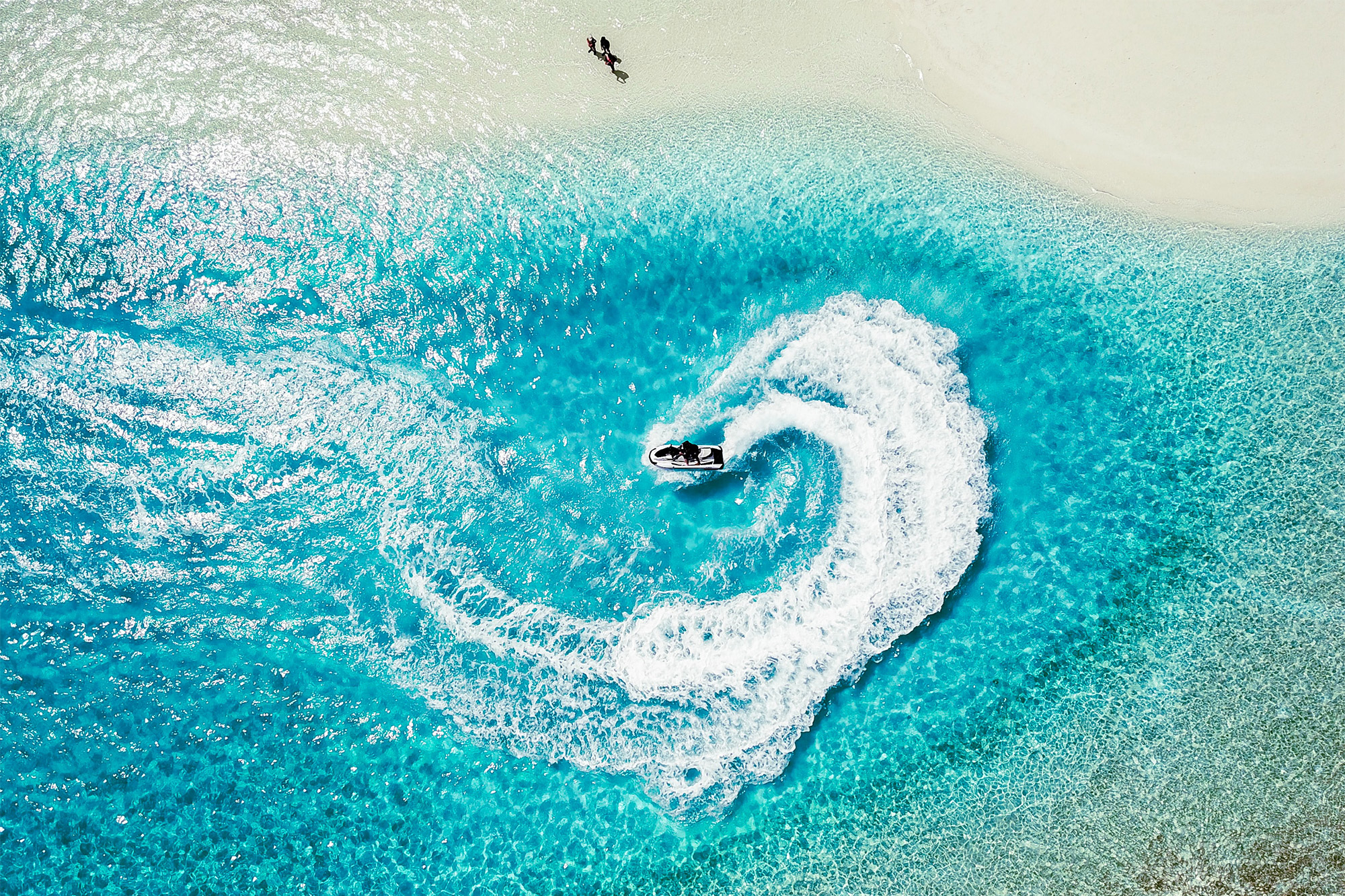 Jet ski zooming around in turquoise sea creating waves.