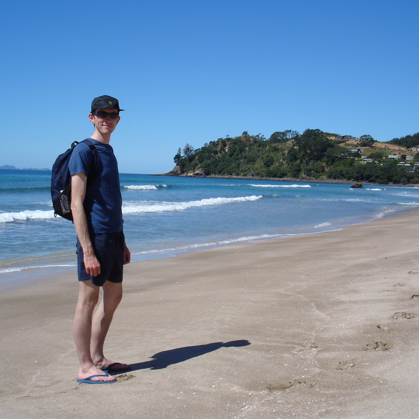 Man stood on beach with blue sky and the sea.