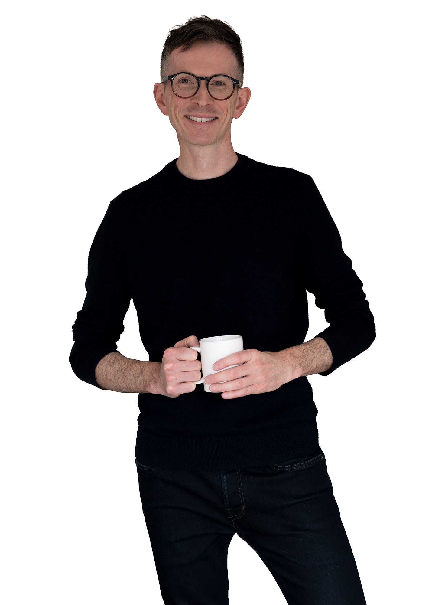 Man stood holding a cup of tea and smiling.