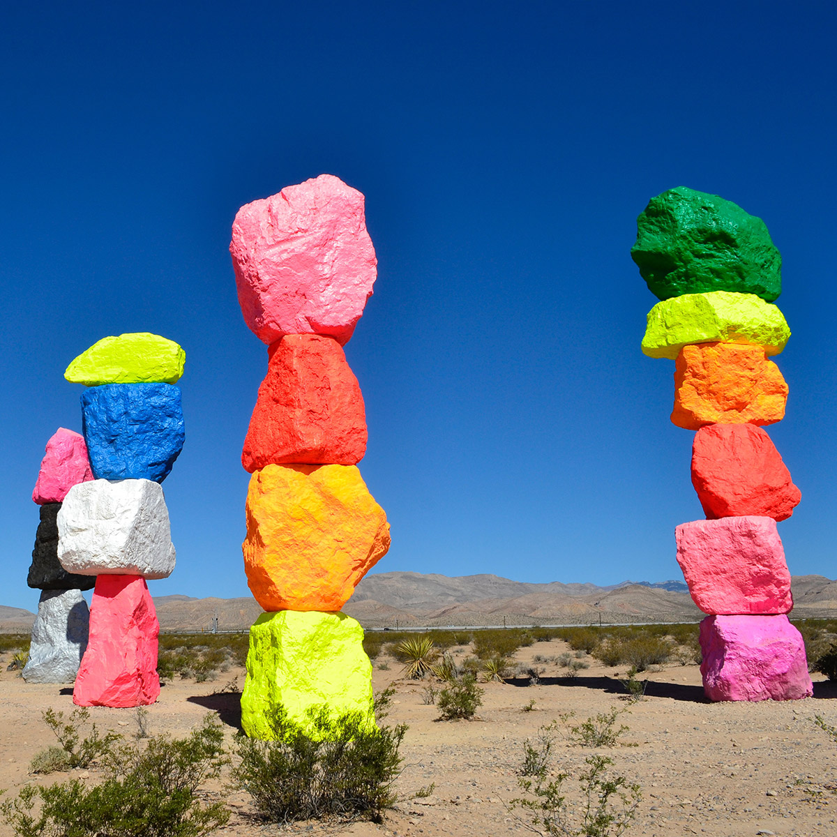 bright coloured painted rocks stacked in columns in the desert