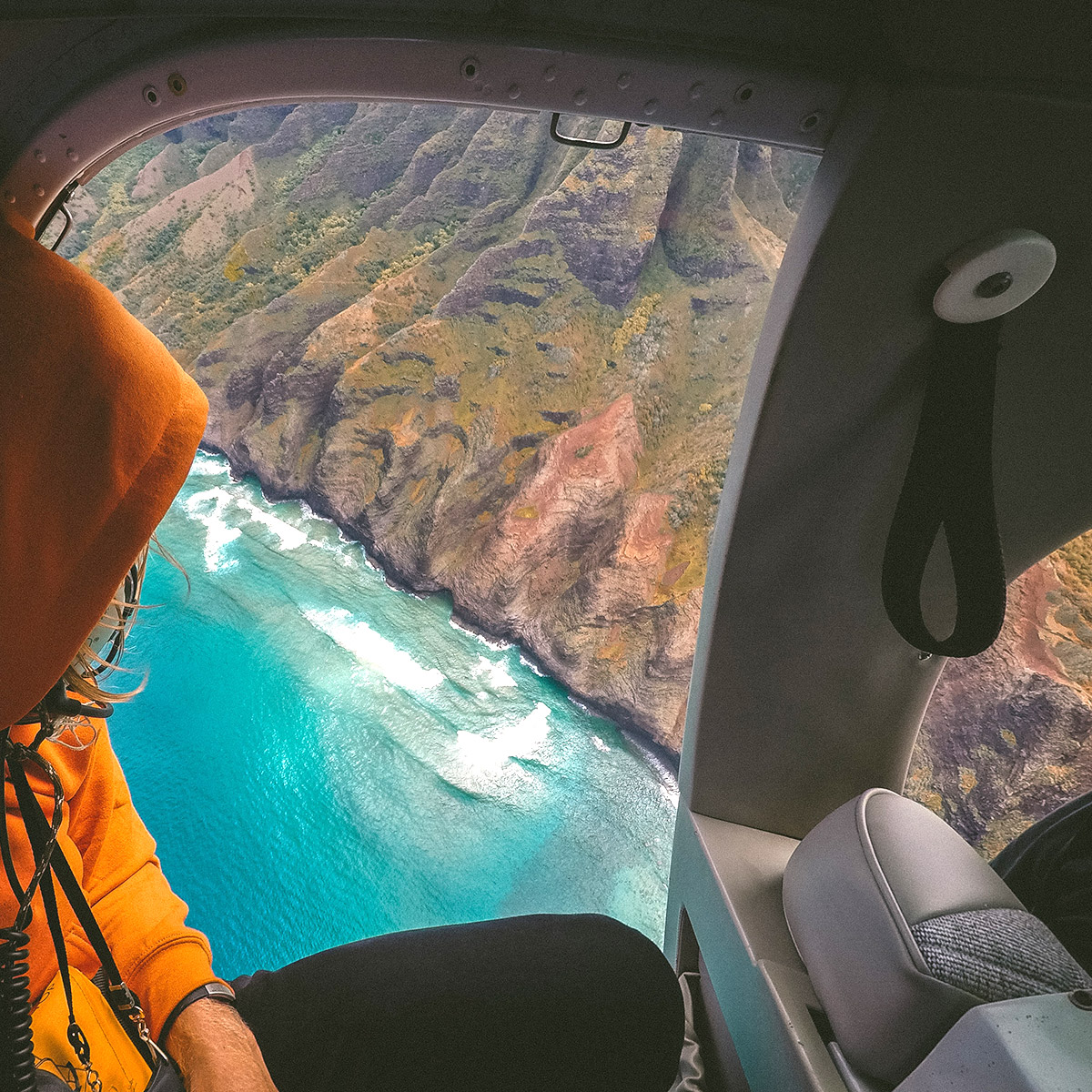 person in orange waterproof jacket looking out of helicopter window at wild coastline