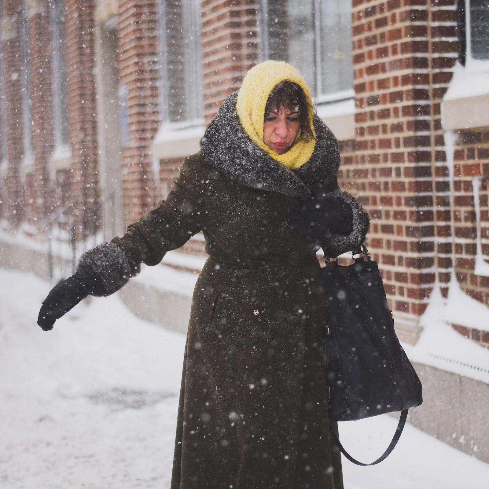 woman walking in the snow in city street