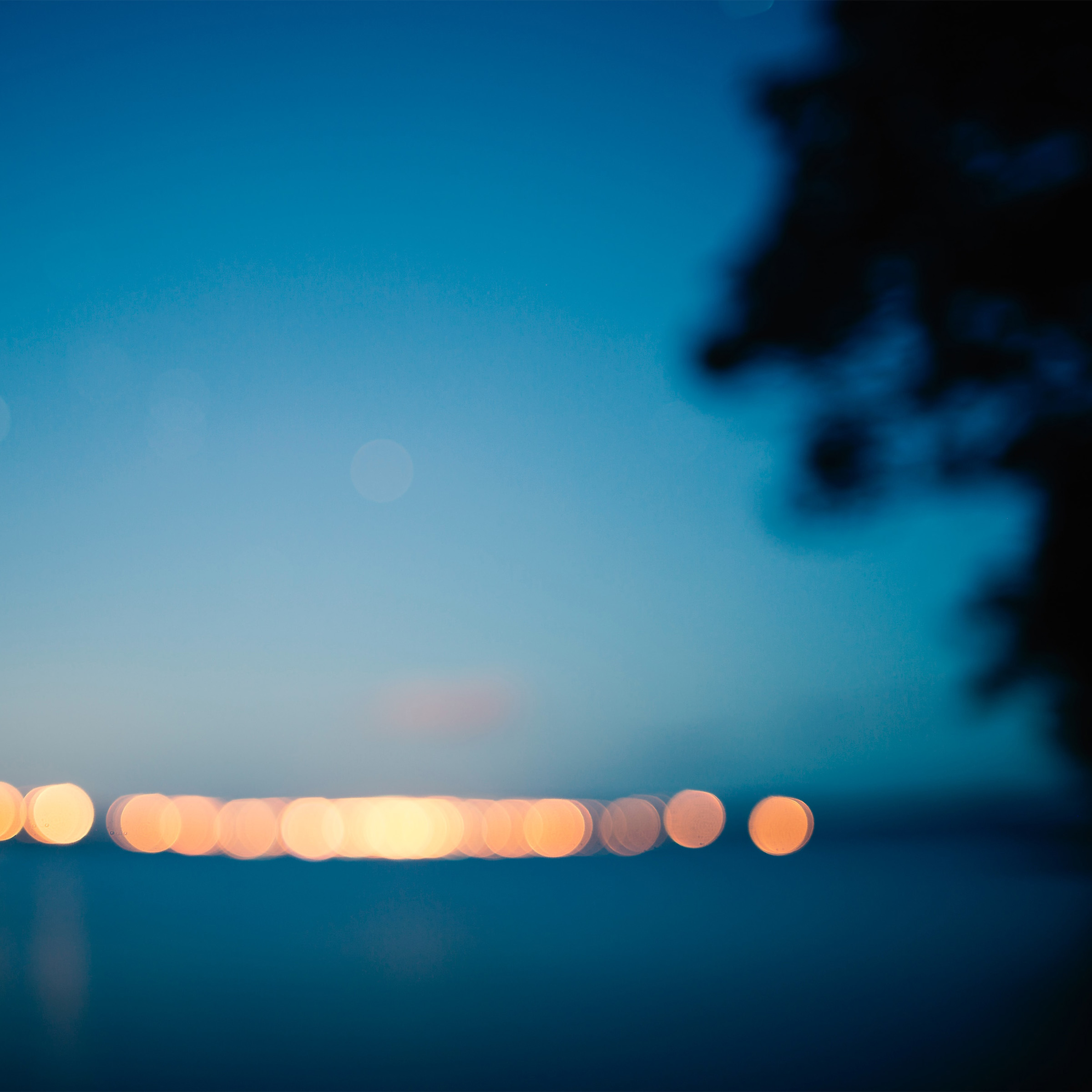 Blurred lights by the sea at dusk