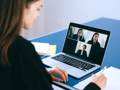 A woman taking notes during a zoom meeting.