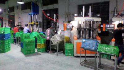 A photo of consumer product mass production line, showcasing many workers each working on a large machine.