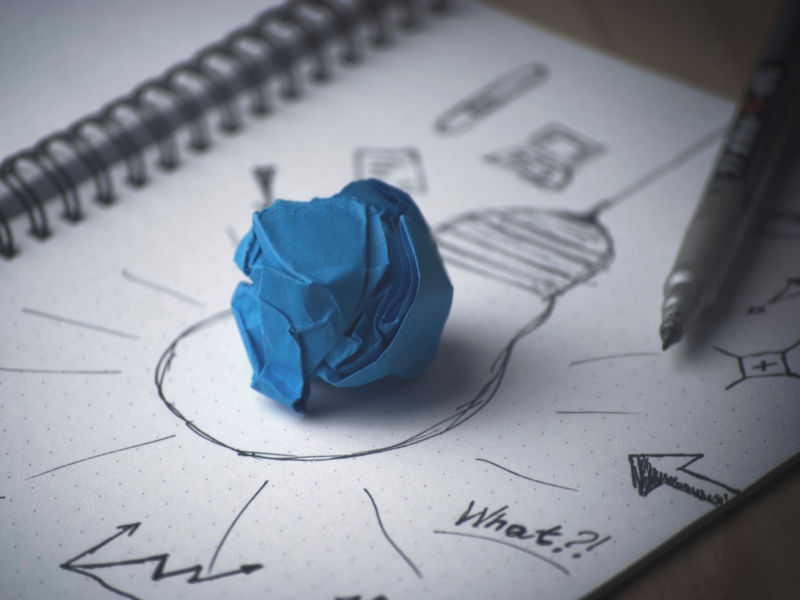 sketch of a light bulb with a blue paper made into a ball above it.