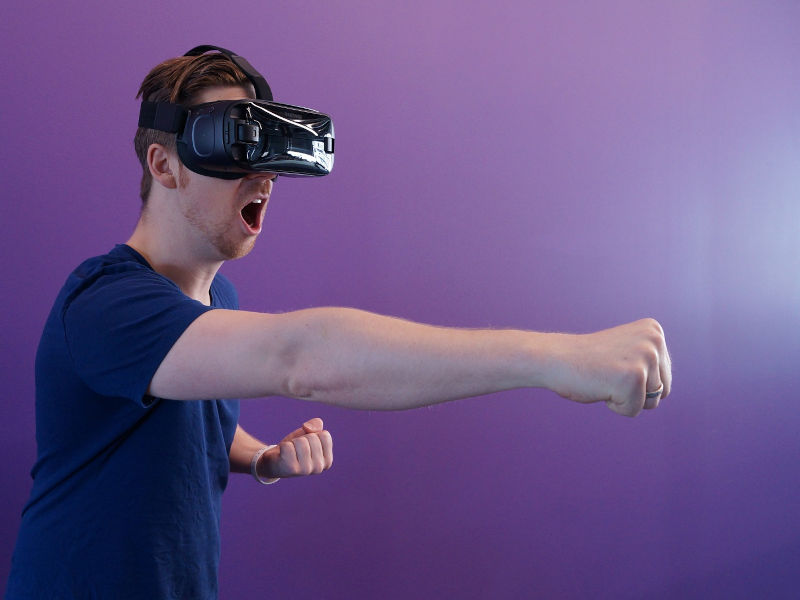 Man wearing VR headset and throwing a punch in the air.