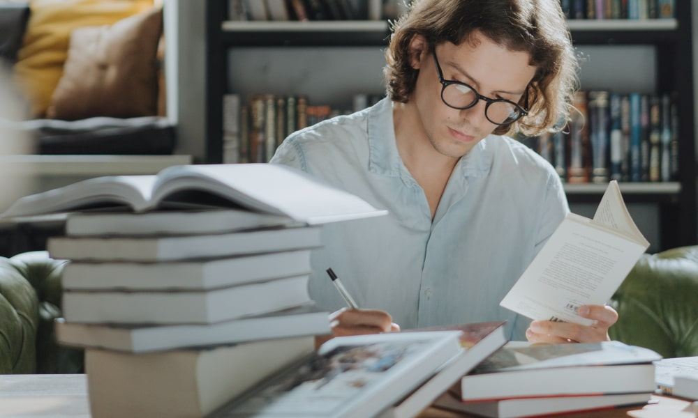 Man with black glasses studying with lots of books in the frame.