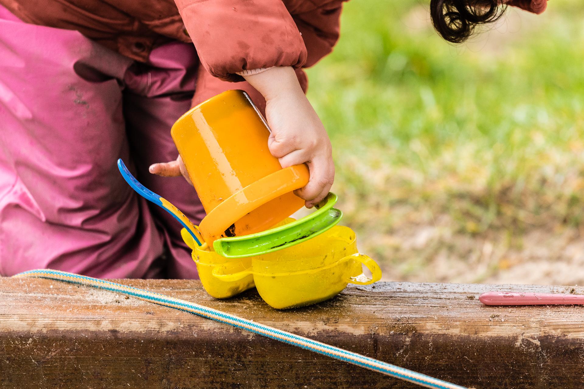 girl playing outside bucket sand