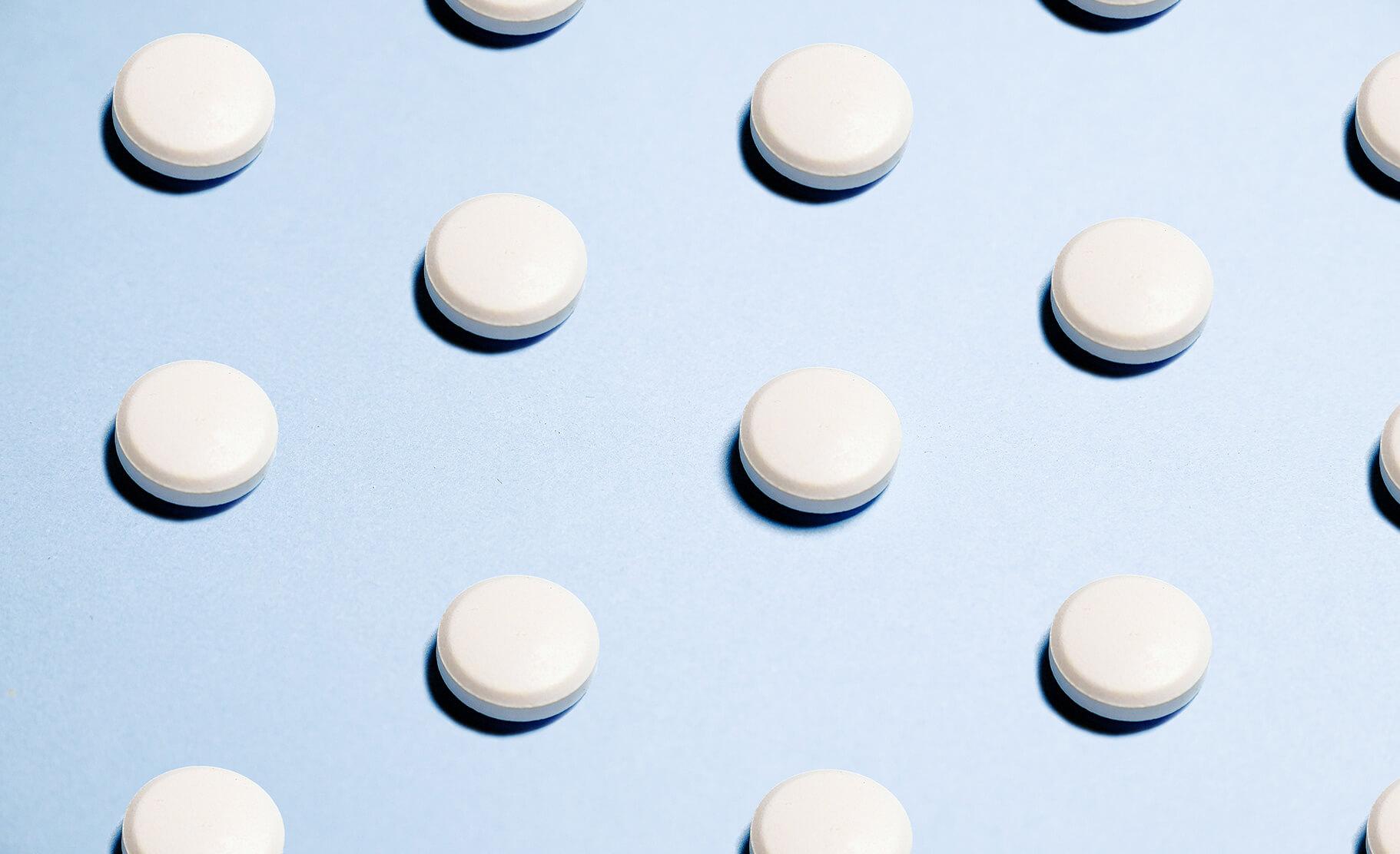 white ketamine-like tablet pills on a blue background