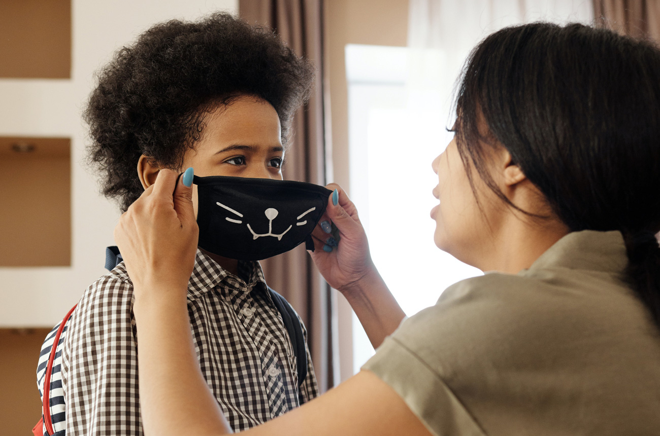Mom putting on son's mask
