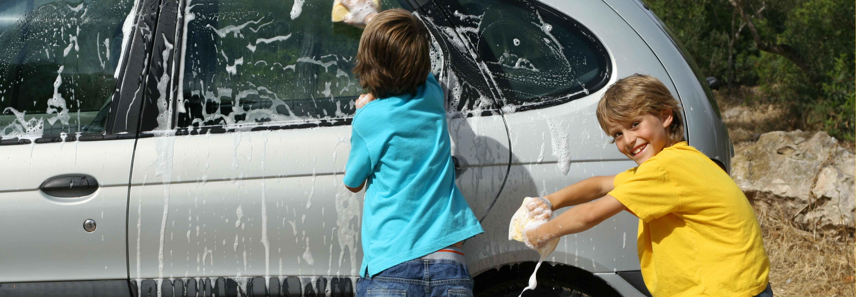 2 kids washing a car