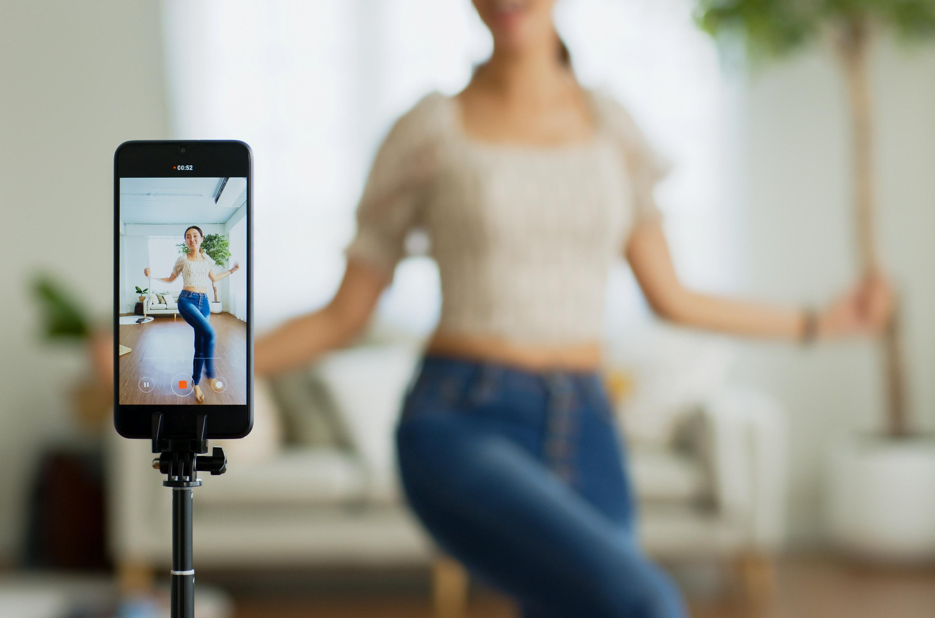 Teen girl recording a clip for a TikTok dance challenge
