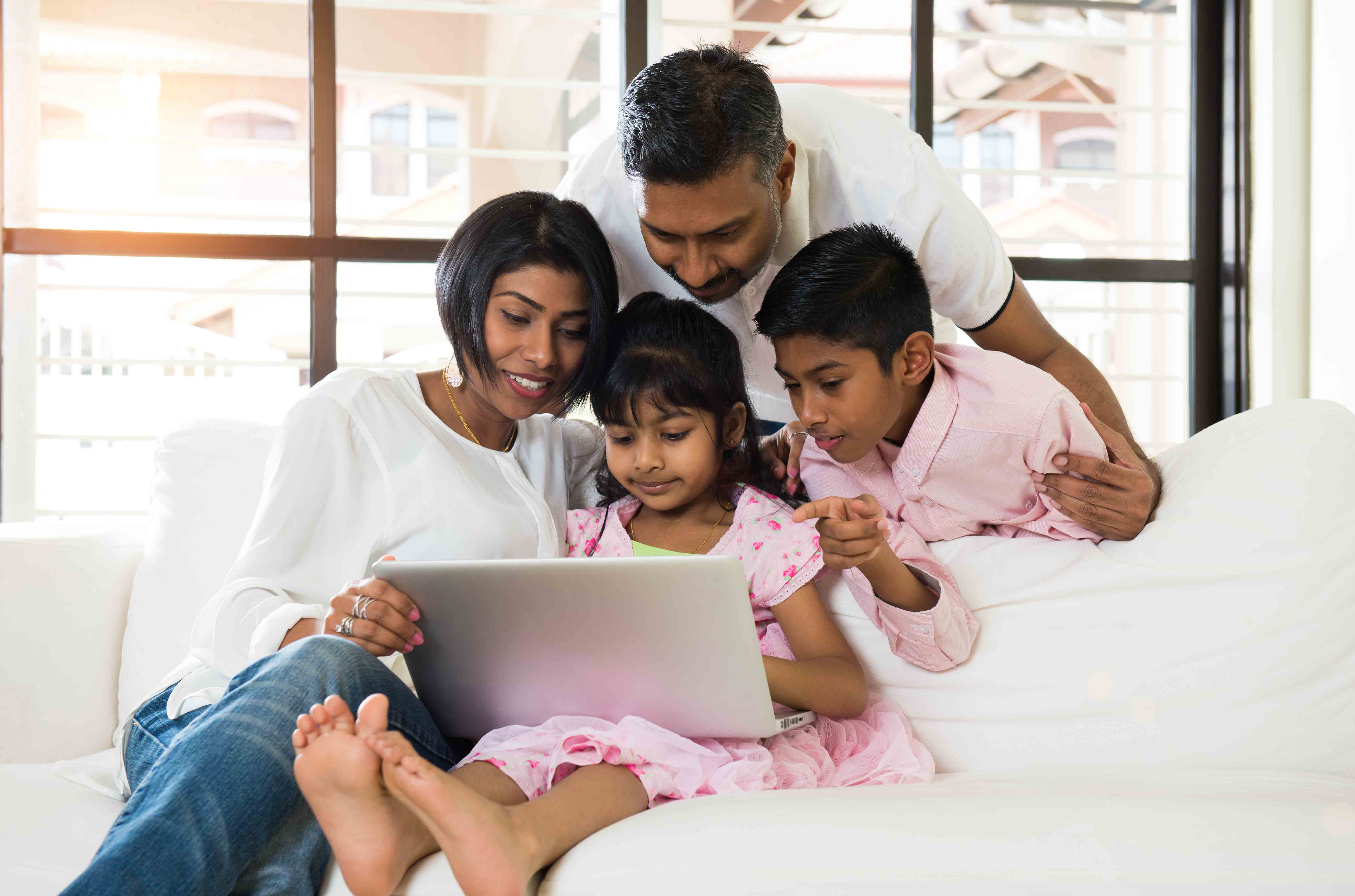A new immigrant family researching the Canadian financial system on a laptop