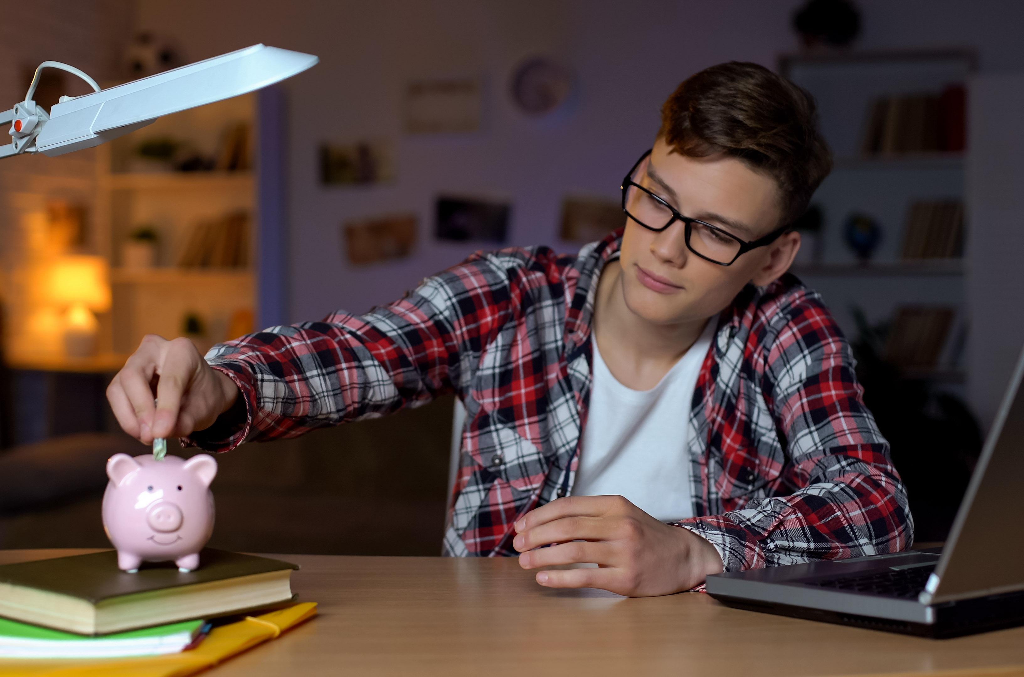 teenager saving coin into piggy bank