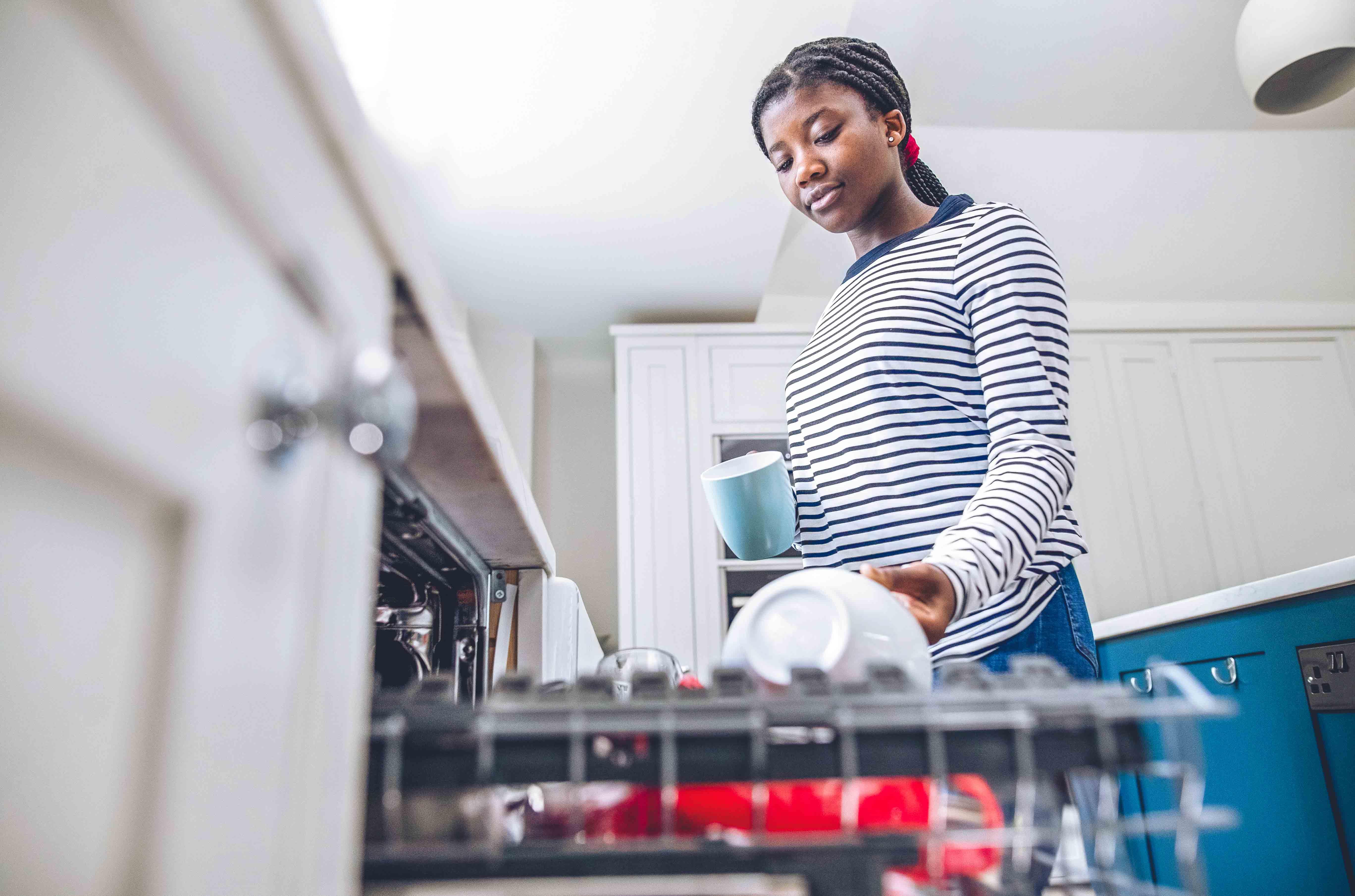 Teenager loading dishwasher