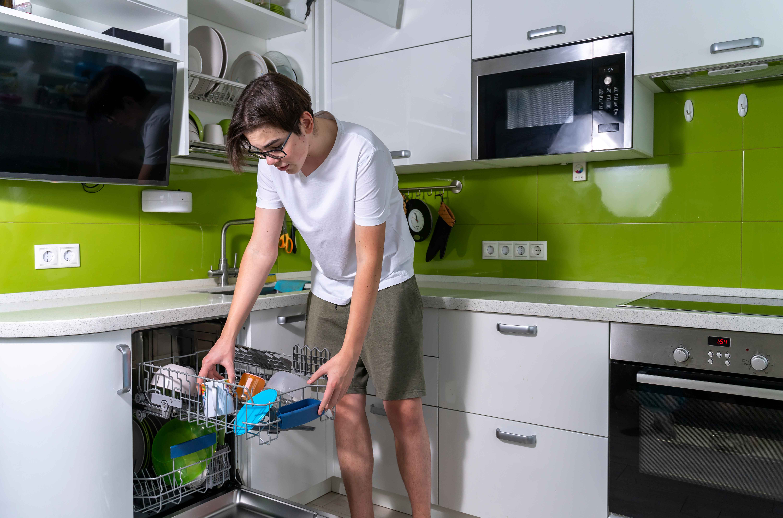Teenager using dishwasher
