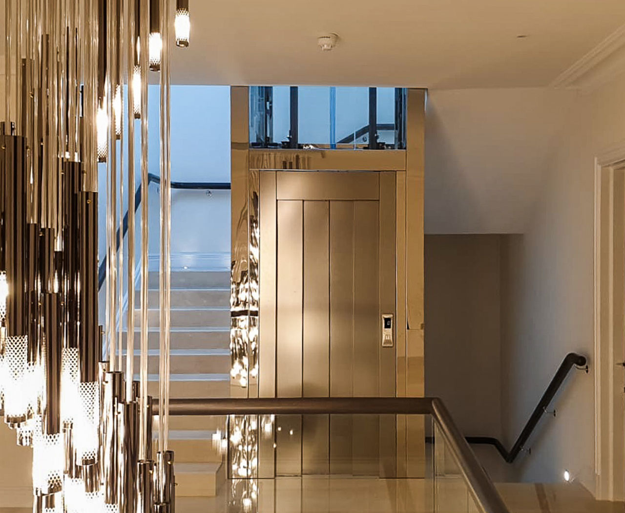 Glass structure home lift inside a stone staircase