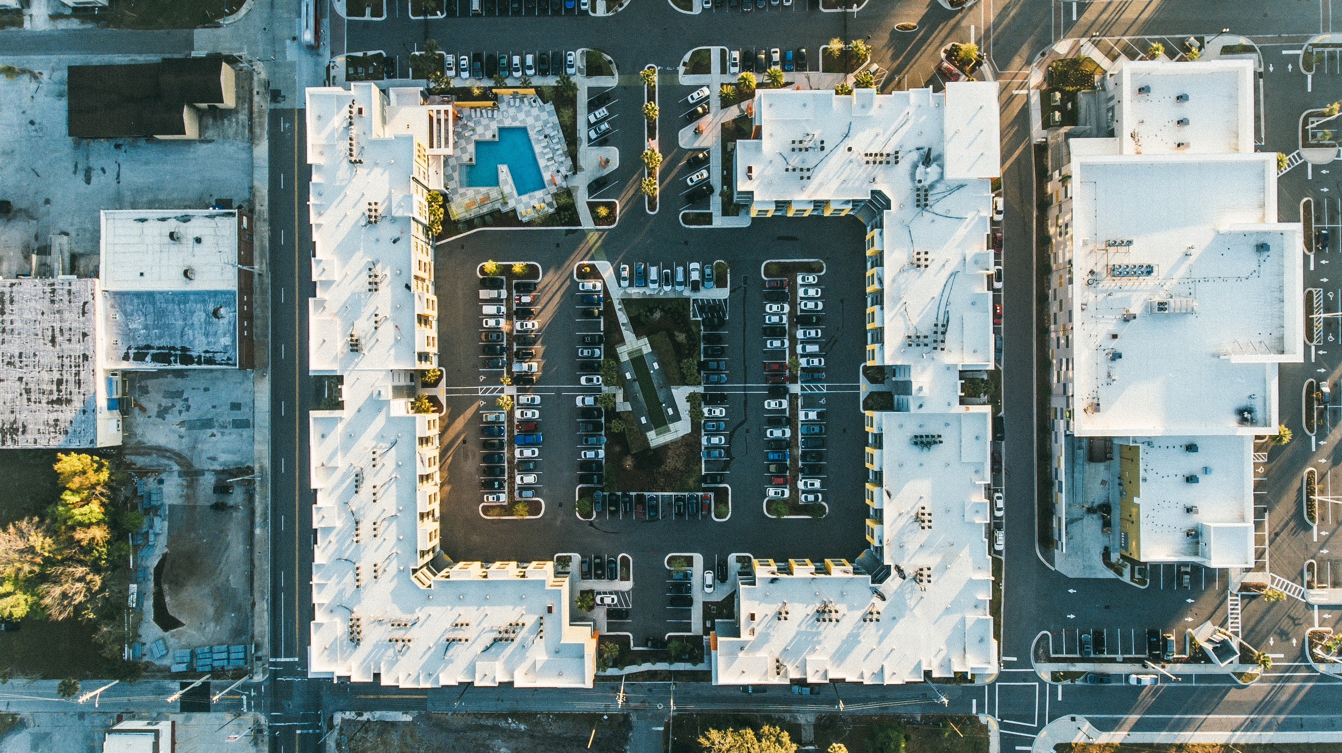 Aerial shot of a contemporary, low-rise community with courtyard parking and a pool