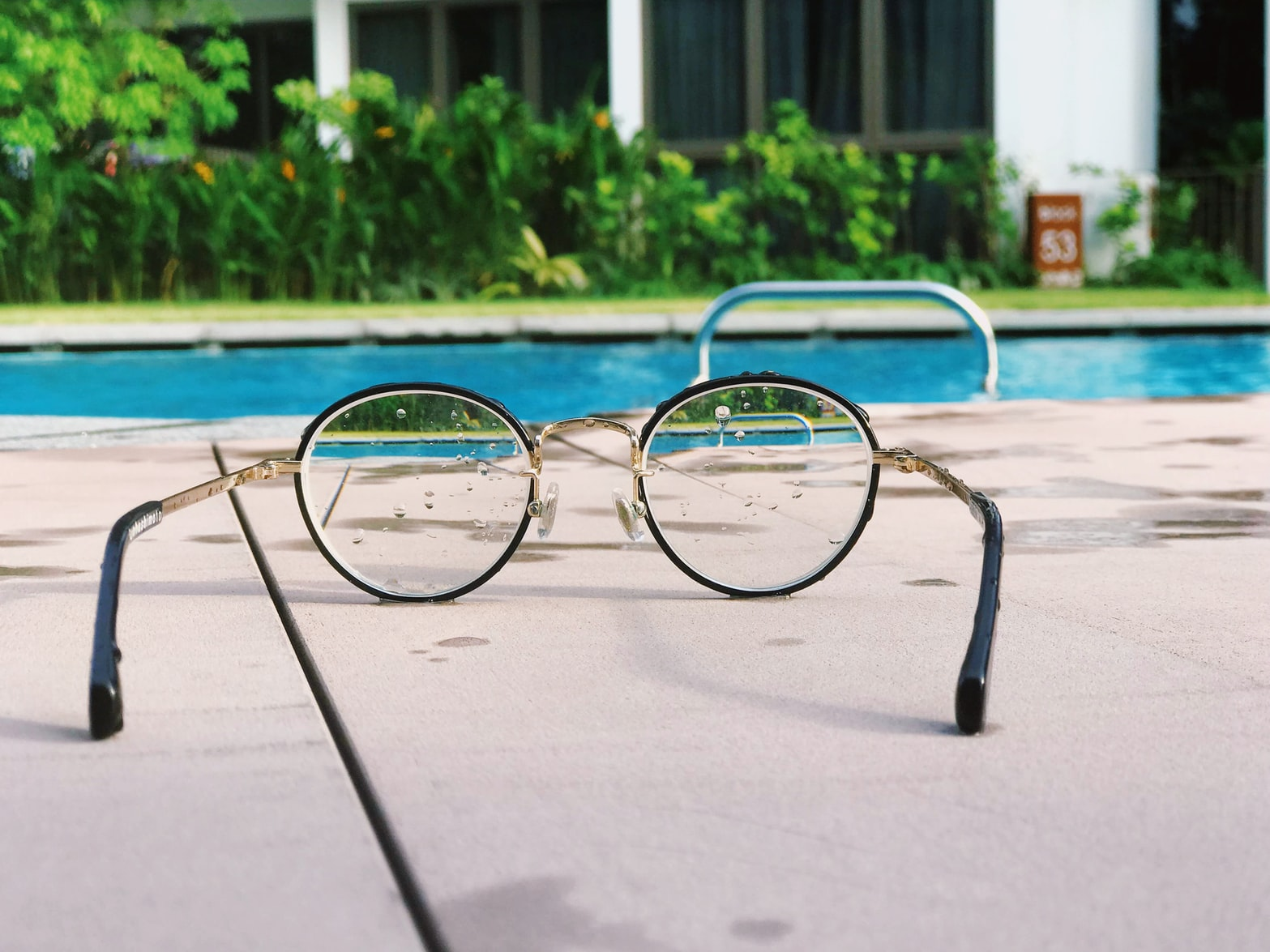 View of a swimming pool through eyeglasses on the pool deck, because the SightPlan blog brings industry news into focus