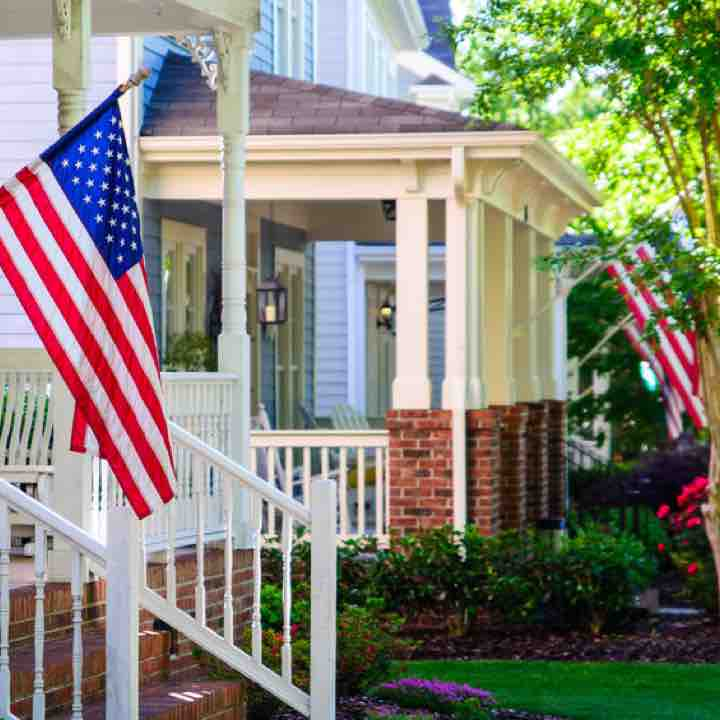 Cozy front porches with American flags on a tree-lined street