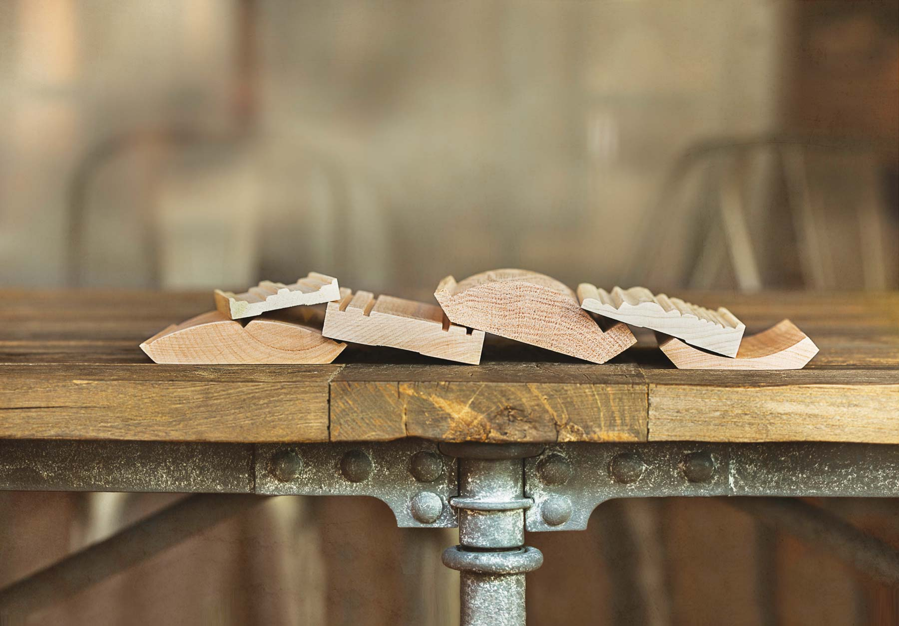 A stack of wood moulding samples on an industrial table