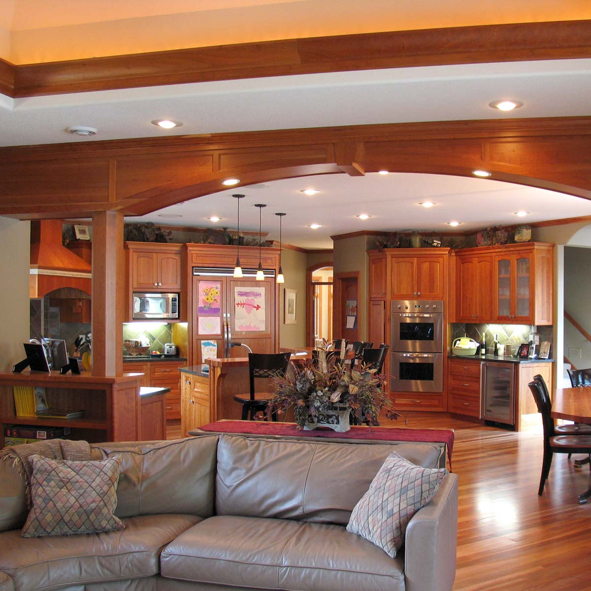 Expansive family room with a wide, gentle wooden arch separating sections of the room