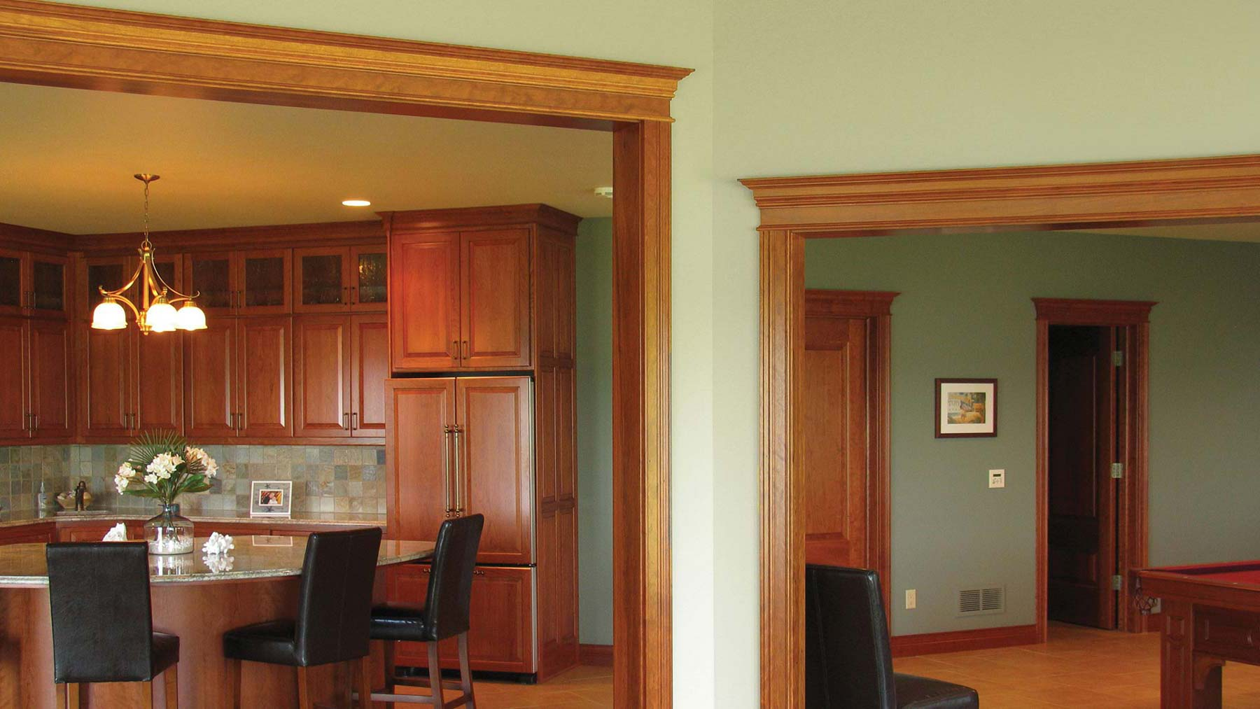 Green and gold earth-toned rooms with hardwood door frames and window casings