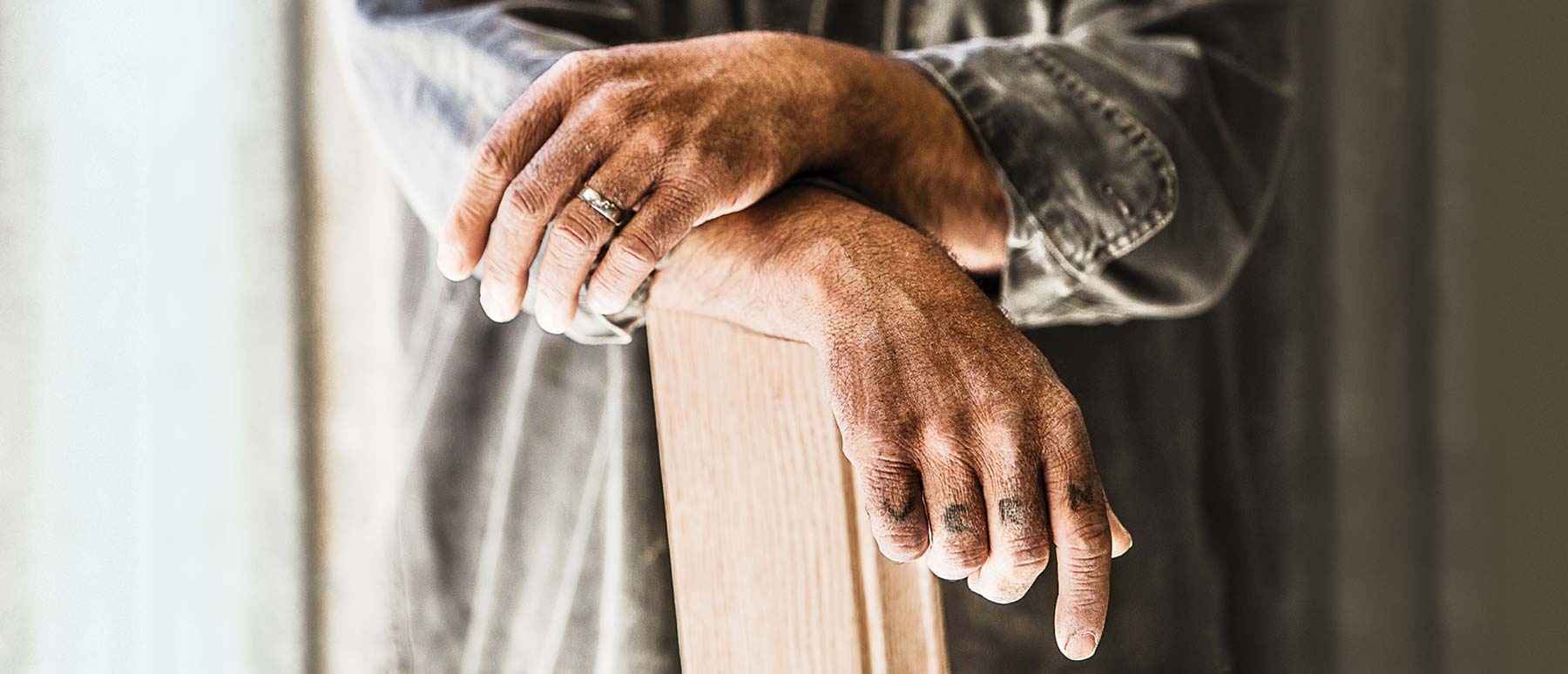 Tattooed, weathered hands resting on an elegant piece of fine hardwood