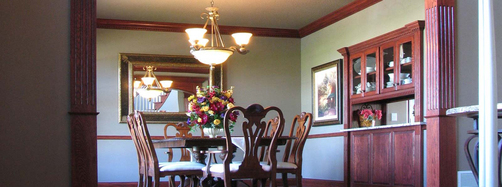 Elegant, arched cherry door frame looking into a formal dining room