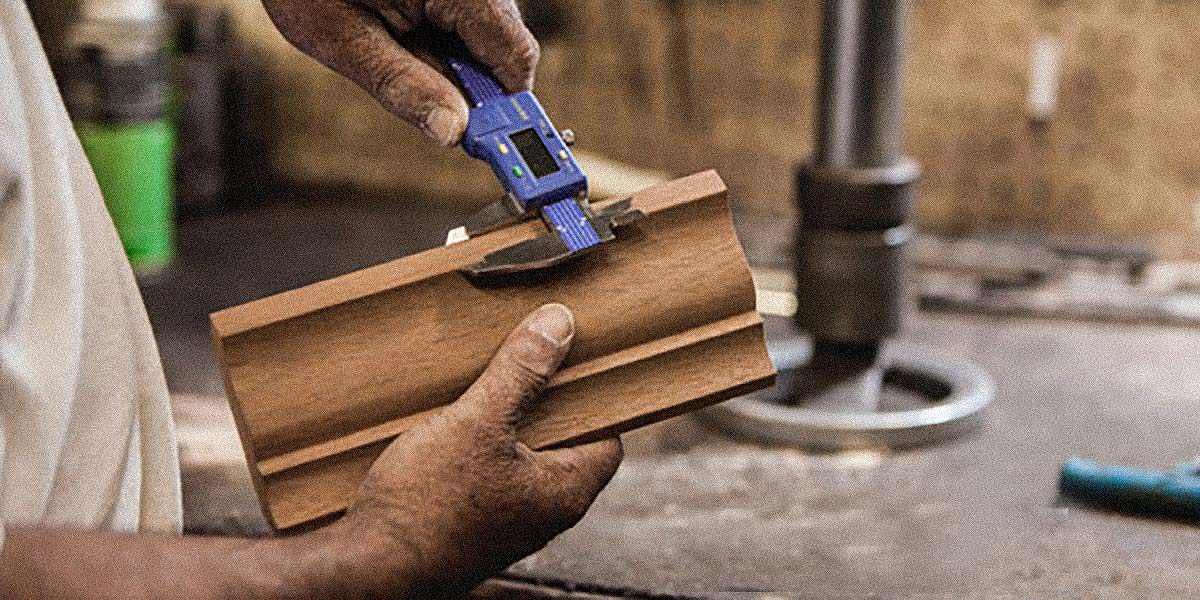 Two hands working with precision on a custom piece of hardwood moulding