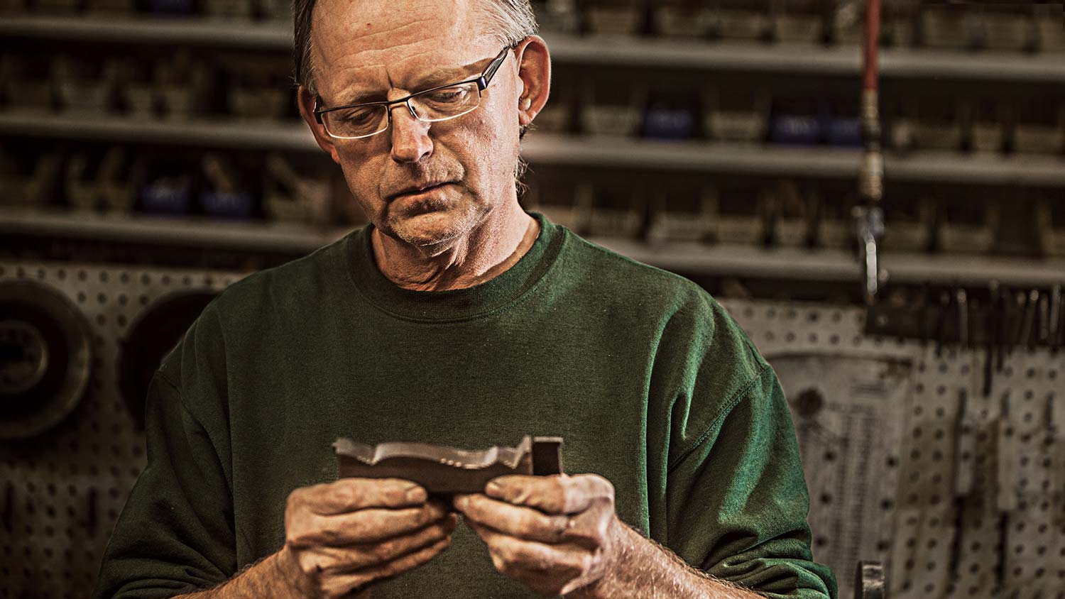 Contemplative employee looking thoughtfully at a moulding sample, framed like an interview