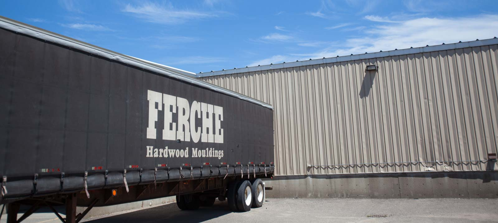 Semi-truck trailers backed into the plant, ready to ship wood mouldings across the country