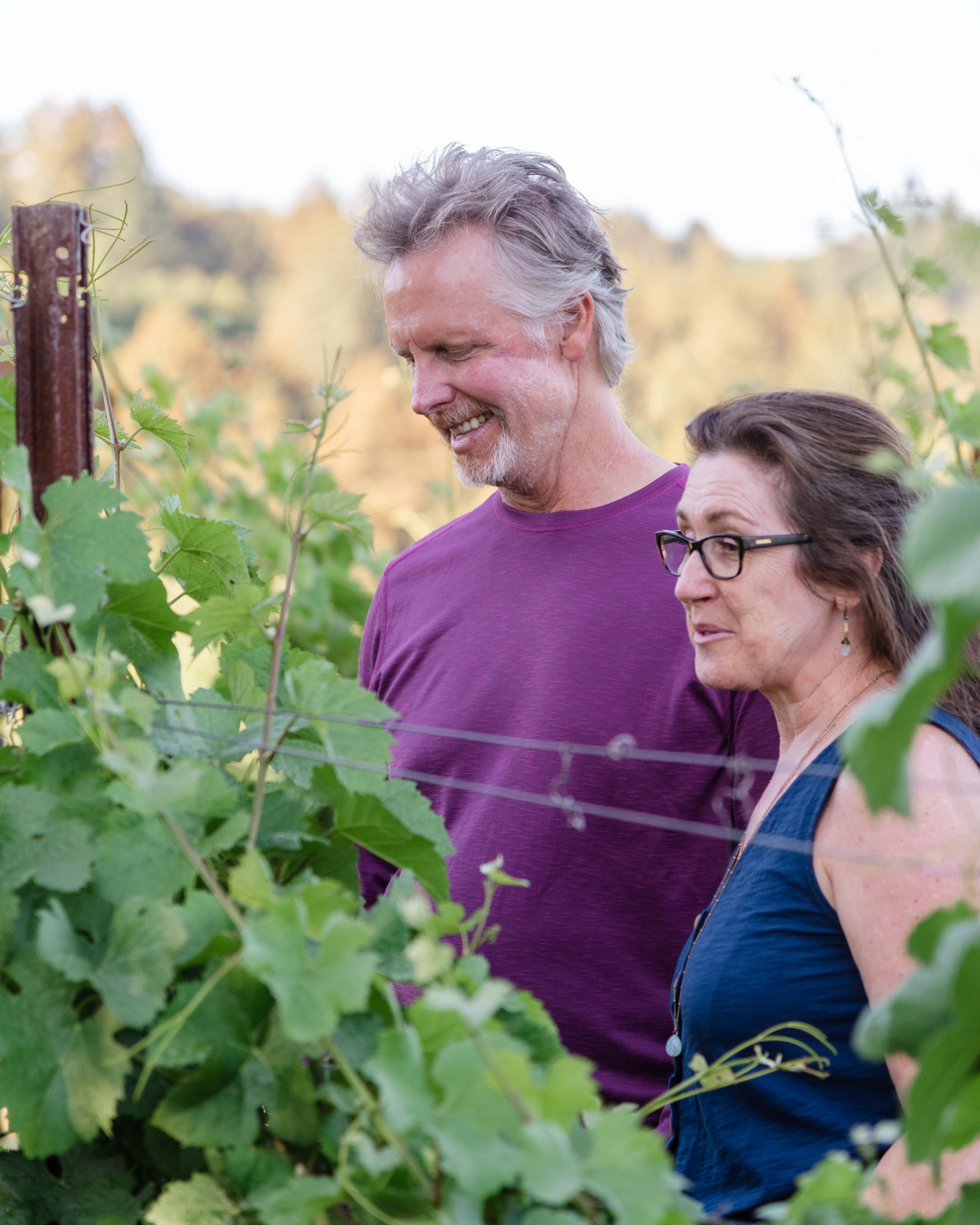 Chris Baker and Tina Cacace of Aptos Vineyard, inspecting some vines