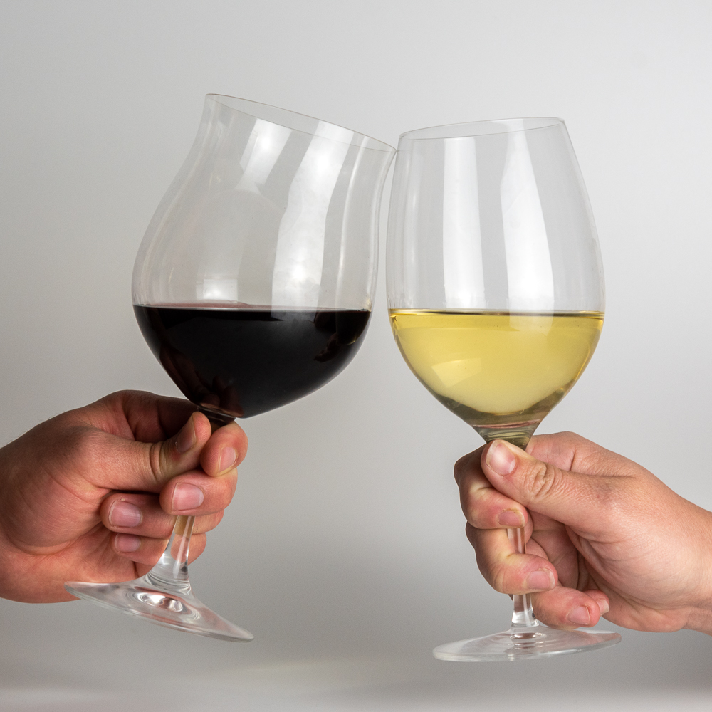 Two wine glasses cheers-ing together, one with pinot noir and one with chardonnay