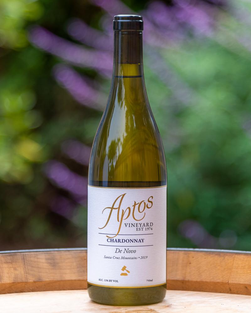 Aptos Vineyard 2019 Chardonnay wine bottle placed on top of a wine barrel