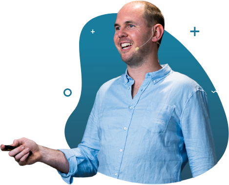 A happy man wearing earpiece lapel holding a remote control for his presentation seemingly explaining something to an audience