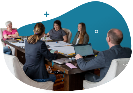 a group of 5 people in an office setting doing a meeting