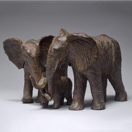 Sculpture réalisée par Sophie Verger en bronze, d'un éléphanteau réfugié entre son père et sa mère éléphants.