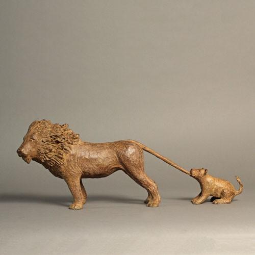 Sculpture réalisée par Sophie Verger en bronze d'un lionceau qui essaye de retenir son père en lui mordant la queue.