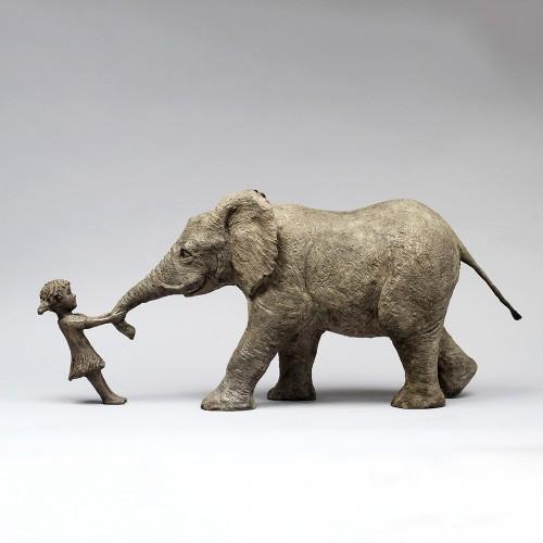 Sculpture en bronze d'une petite fille qui tire la trompe d'un éléphant, réalisée par l'artiste Sophie Verger.