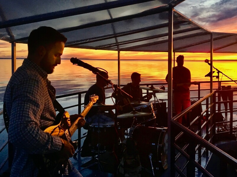 Live band playing on a boat cruise at sunset.