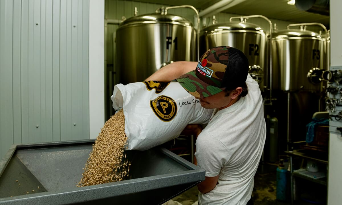 Brew master adding hops as he makes beer at Manitoulin Brewing Distillery.