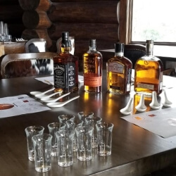 Shot glasses laid out on a table along with 4 premium scotches ready to be sampled by tour guests.