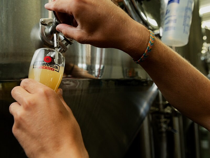 Brew master pouring a cold fresh beer for a visitor to the Manitoulin Brewing Company.