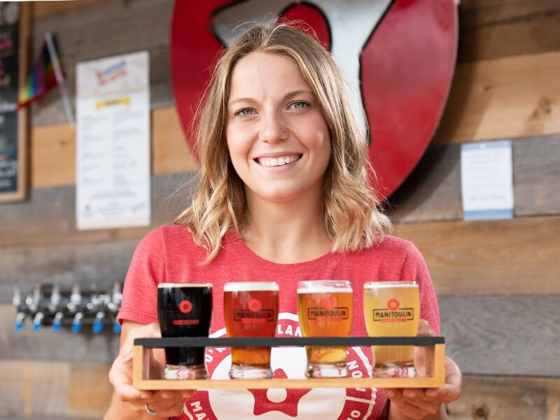 Female waitress at Manitoulin Brewing Company serving fresh cold beer at the end of a tour.