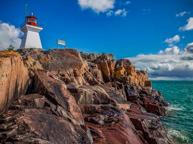 Lighthouse at Killarney with deep blue sky and waters crashing against rocks.