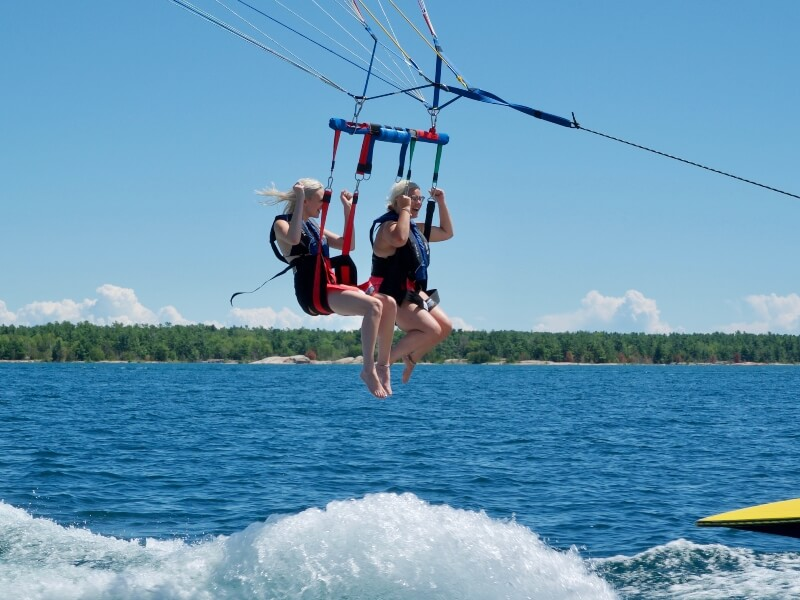 Two women parasailing behind a boat on a warm summer afternoon near Killarney Mountain Lodge.