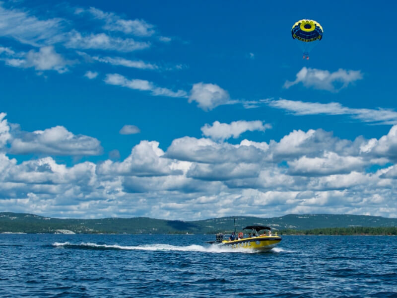 Two women parasailing behind a boat over the deep blue waters of Georgian Bay near Killarney Mountain Lodge.