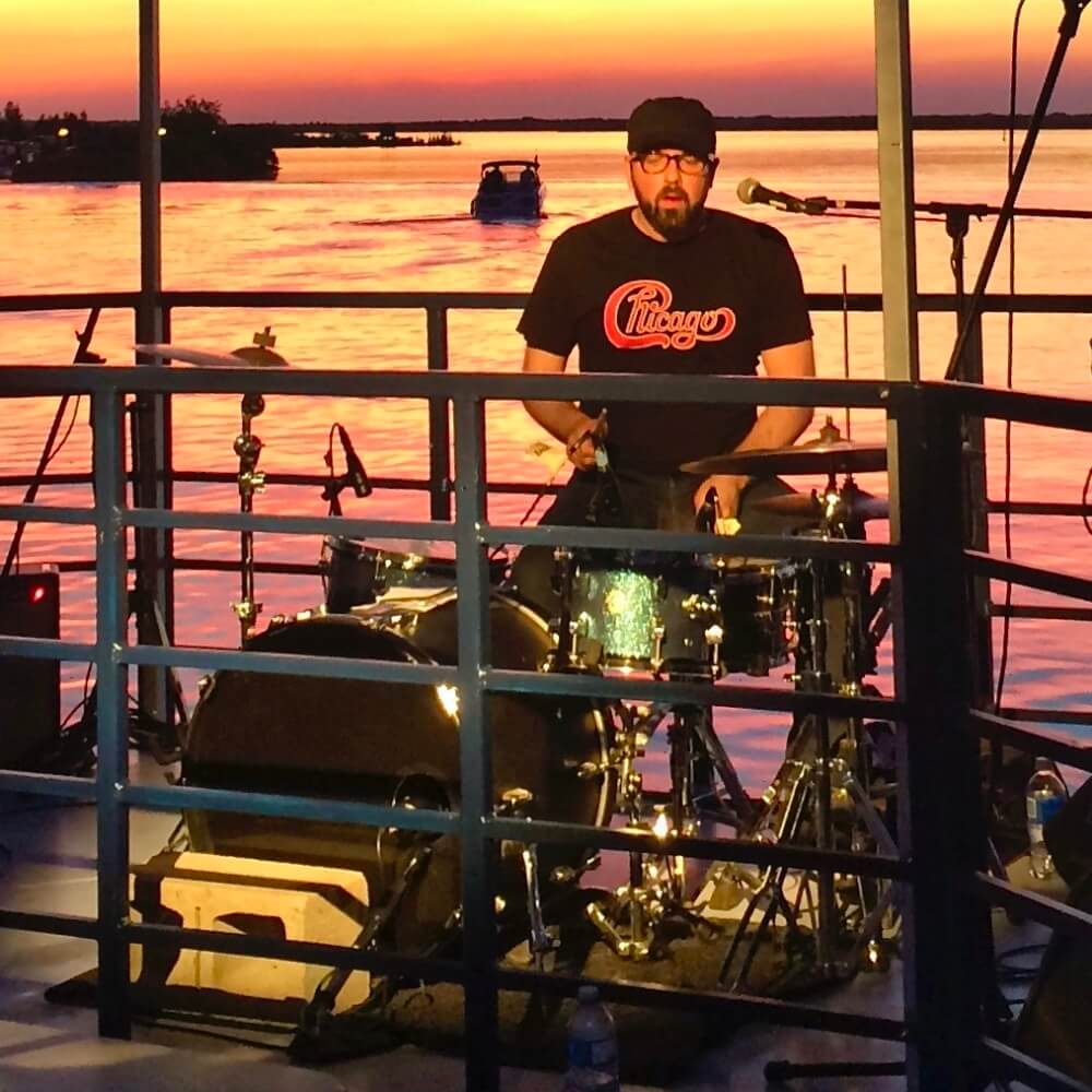 Drummer in a live band playing music during a sunset dinner cruise.
